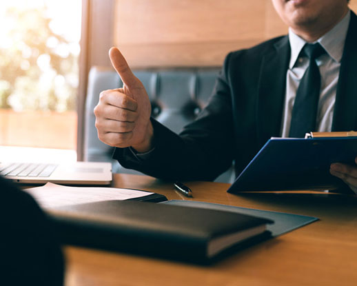 A businessman giving a thumbs-up for a report in the office room
