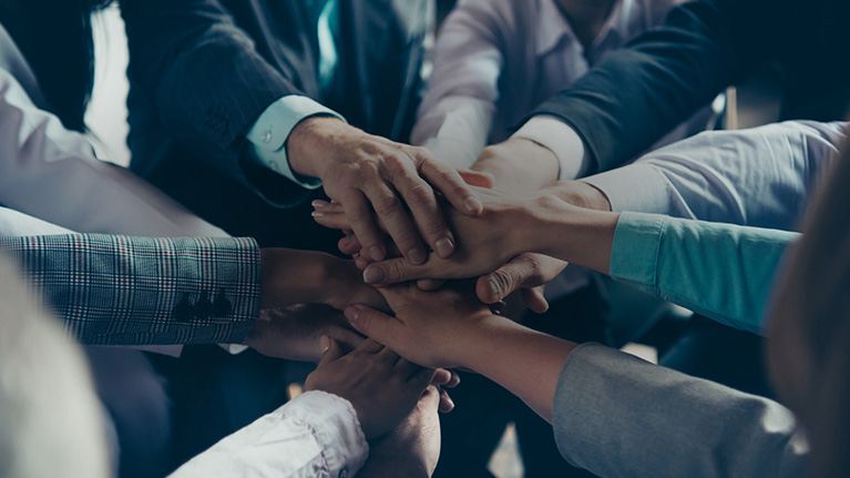 Group of professionals making a pile of hands